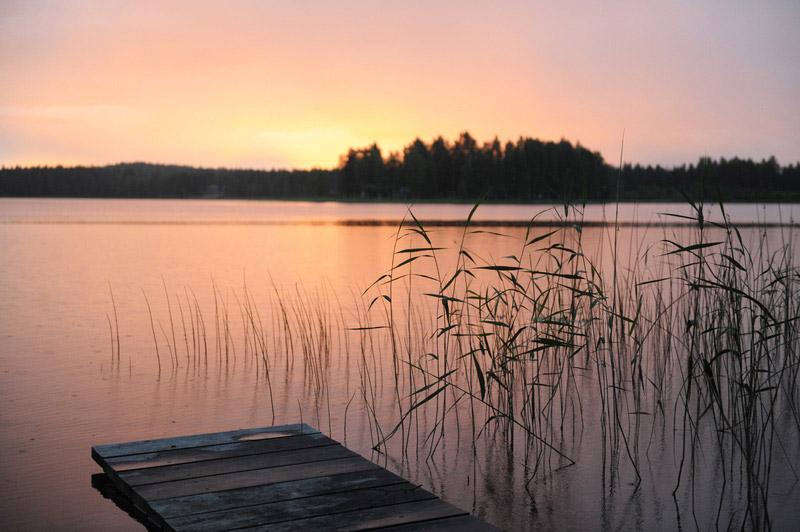 Uitzicht over een meer vanaf een aanlegsteiger bij zonsopgang