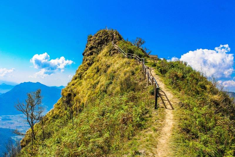Smal pad naar een bergtop. Sfeerbeeld bij het blog: Loslaten en lichter leven van coach en relatietherapeut Lisette Wevers in Amsterdam