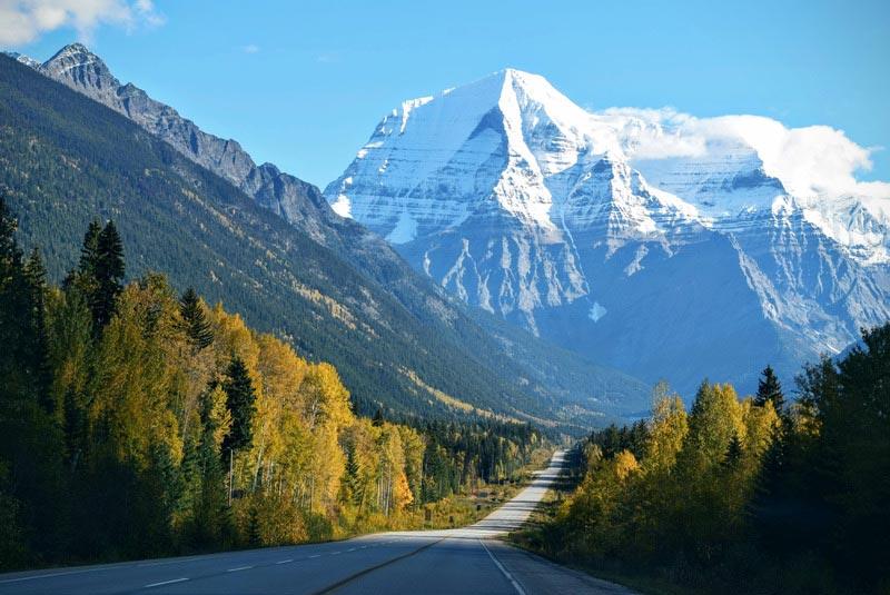 weg door natuur richting bergen met besneeuwde toppen