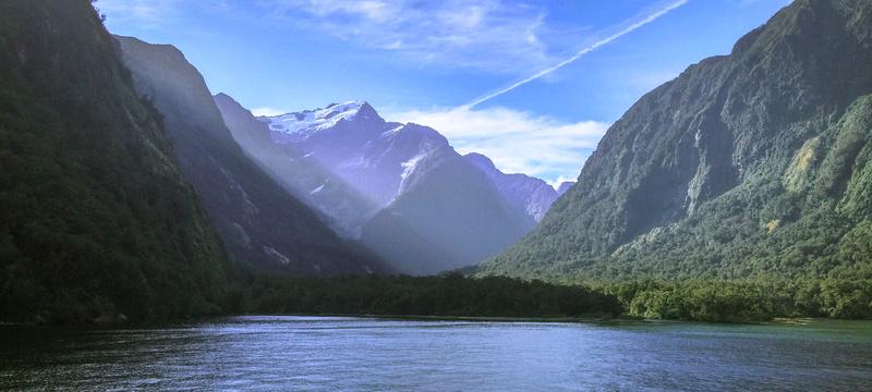 Uitzicht op besneeuwde bergtoppen vanaf een meer.