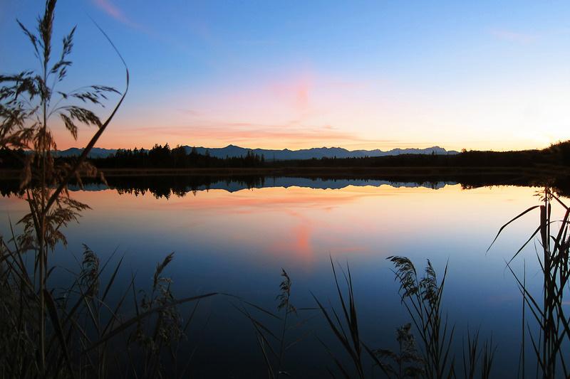 Uitzicht over een meer met zonsondergang
