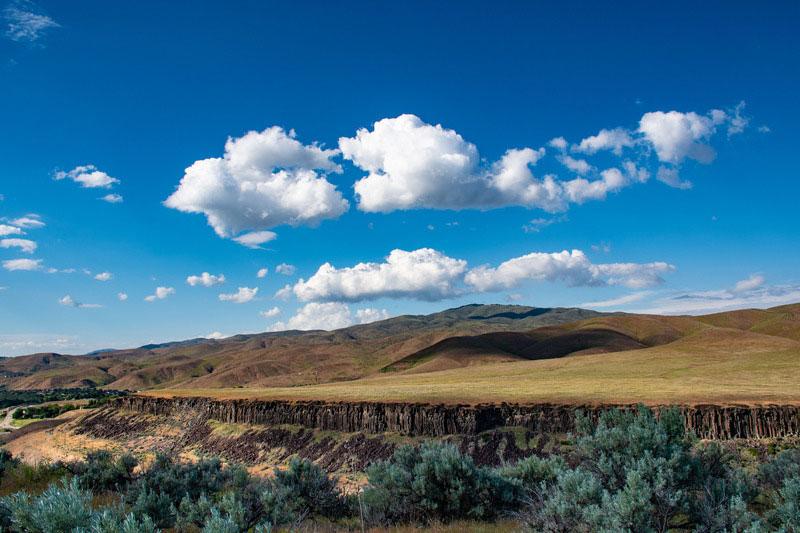 Uitzicht over een vallei onder een blauwe lucht