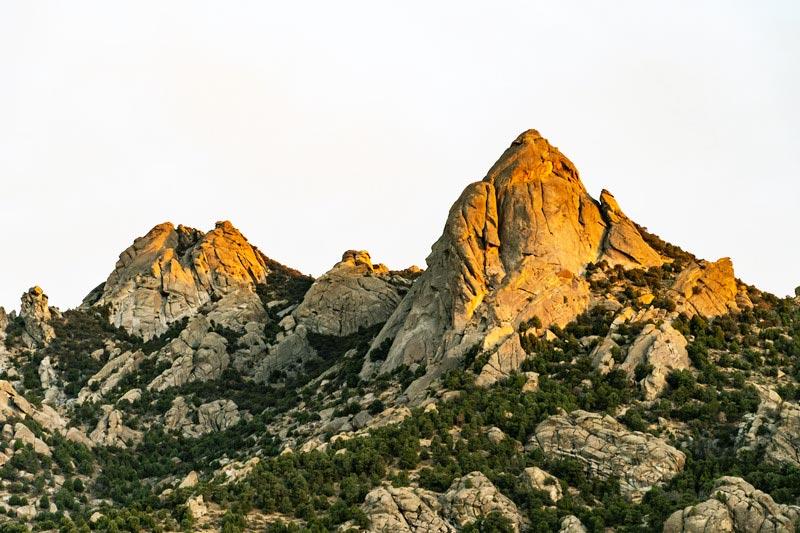 Rotsige heuvels met door zonsondergang beschenen toppen.
